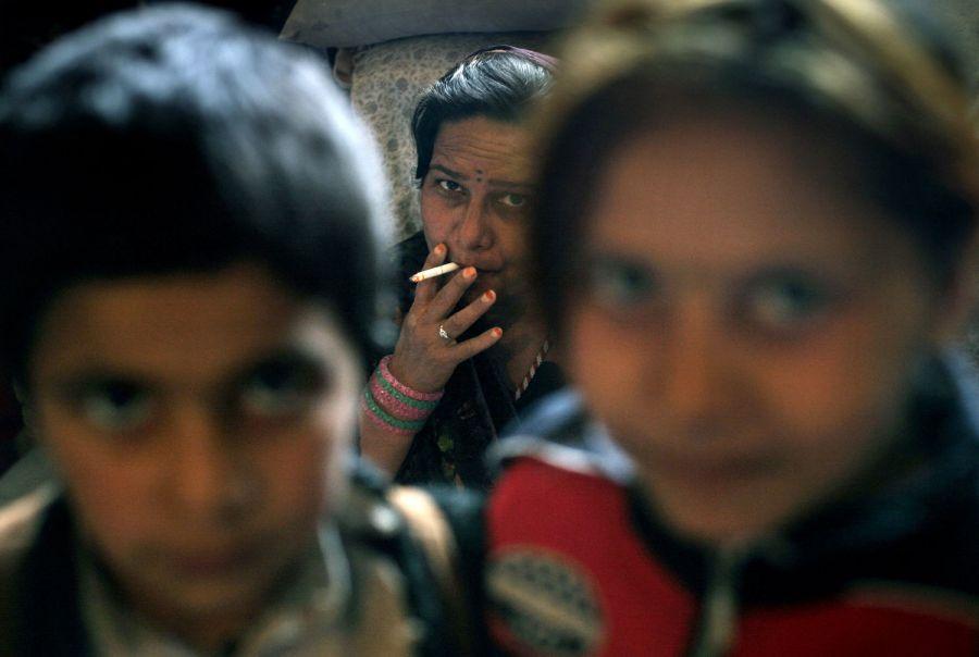 8) Ширингул, отбывающая 20 летнее заключение за соучастие в грабеже и серийных убийствах таксистов, курит рядом со своими двумя детьми – 7-летней Малиной, слева, и 6-летним Хекматулахом в своей камере в кабульской тюрьме Пул-и-Чаркхи. В связи с делом Ширингул были казнены пять человек, в том числе ее муж, двоюродный брат, деверь и сын, который был арестован вместе со своей матерью в возрасте 13 лет и затем казнен, когда ему исполнилось 18. (AP Photo/David Guttenfelder)