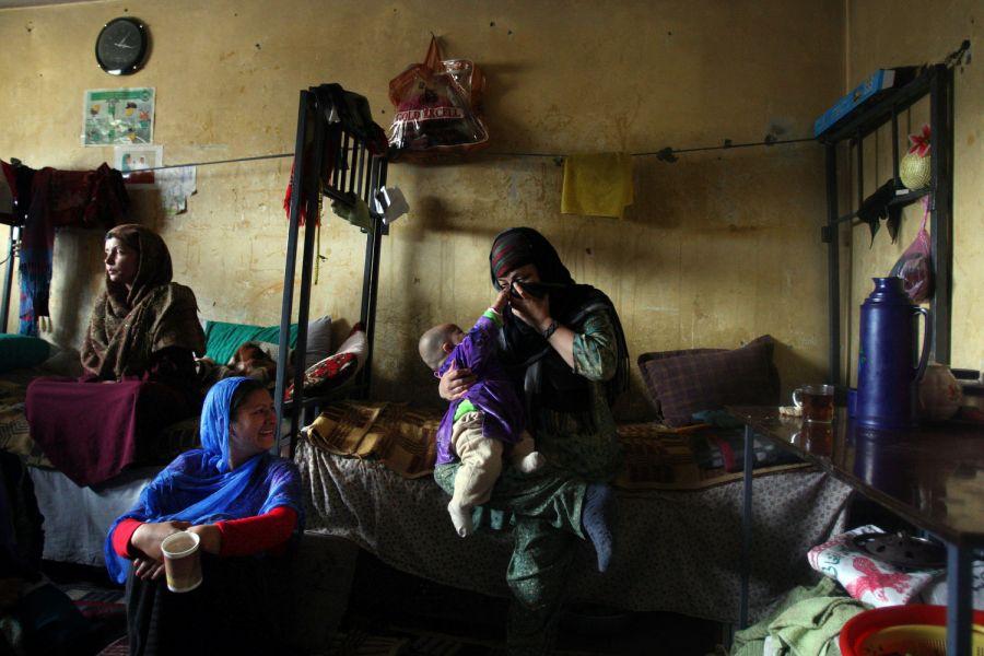 9) Ребенок заключенной по имени Макай пытается убрать от лица платок, которым закрывается сокамерница его матери в камере кабульской тюрьмы Пул-и-Чаркхи. 27-ляя Макай была арестована по обвинению в бегстве из дома, но позже была освобождена согласно помилованию президента Хамида Карзая. (AP Photo/David Guttenfelder)