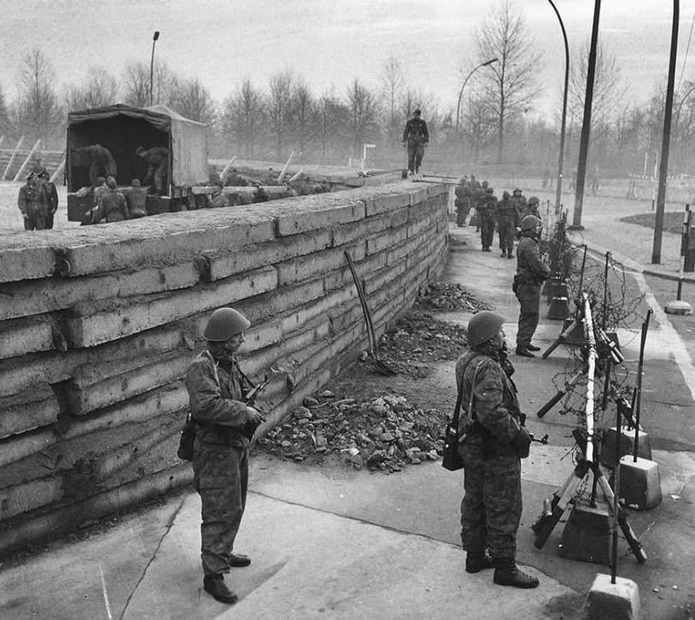 2. За время своего существования с 1961 по 1989 годы стена остановила практически всю эмиграцию и отделяла Восточную Германию от Западной более четверти века. На этом снимке полиция Западного Берлина стоит за колючей проволокой у большой бетонной стены у Бранденбургских ворот 23 ноября 1961 года. Коммунисты только что разбили ширму, закрывавшую стену. На снимке можно видеть, как материал, использовавшийся для строительства стены, грузят на другой стороне бетонного барьера. (AP)