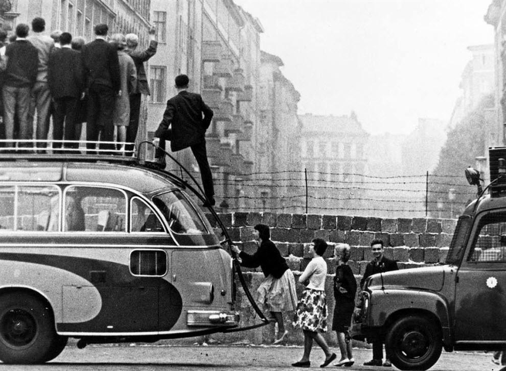 3. Перед возведением стены 3,5 миллионов жителей Восточной Германии избежали ограничений на эмиграцию и сбежали в Западную Германию, через границу между Восточным и Западным Берлином. В то время в Западном Берлине был настоящий экономический бум, частью которого хотели быть жители Восточного Берлина. На фото люди забираются на автобус, чтобы заглянуть за построенную недавно Берлинскую стену. (Keystone, Getty Images)