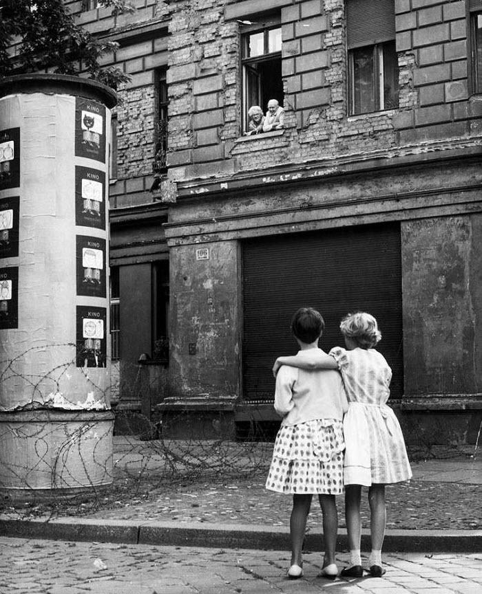 4. Из-за закрытия восточно-западной части границы в Берлине большое количество жителей Восточной Германии больше не могли путешествовать или эмигрировать в Западную Германию. Многие семьи были разделены; жители Восточного Берлина, работавшие в Западной части, были отрезаны от мест своей работы, а жители Западного Берлина оказались изолированы на враждебной земле. Две девочки на улице Западной Германии разговаривают со своими бабушкой и дедушкой в окне дома в восточной зоне, отделенной баррикадой из колючей проволоки, 14 августа 1961 года. (Keystone, Getty Images)