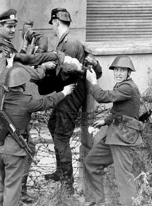 5. После возведения стены около 5000 людей попытались убежать. В результате погибло от 98 до 200 человек. На этом фото умирающего Питера Фехтера уносят солдаты пограничной службы Восточной Германии, которые стреляли в него, когда тот пытался бежать на запад 17 августа 1962 года. Двух бывших солдат пограничной службы обвинили в убийстве. Фехтер 50 минут пролежал на нейтральной территории, после чего его забрали в больницу, где он и умер. (AP)