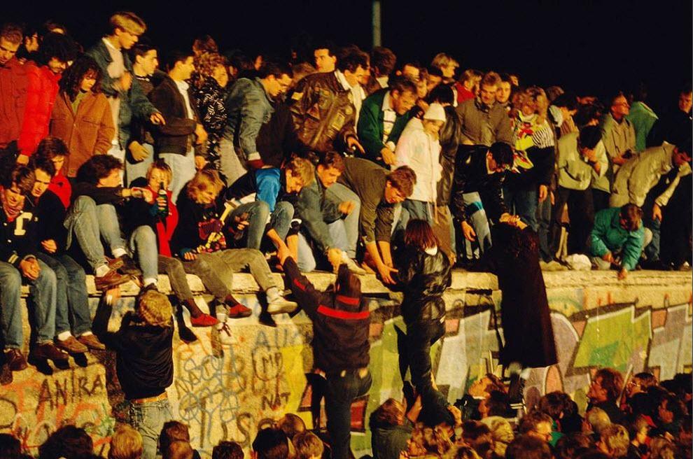 8. Совершенно другая сцена на Берлинской стене 9 ноября 1989 года, когда правительство Восточной Германии объявило после нескольких недель восстаний, что все граждане ГДР могут посещать Западную Германию и Западный Берлин. Толпа празднует падение Берлинской стены. (Tom Stoddart, Getty Images)