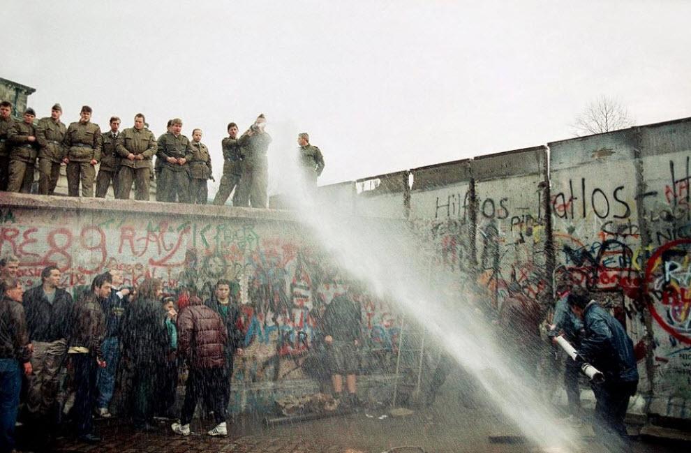 11. Пограничная служба Восточной Германии использует водомет, чтобы разогнать жителей Западного Берлина недалеко от Бранденбургских ворот в Берлине 11 ноября 1989 года. Жители западной части пытались снести стену. (Lionel Cironneau, AP)