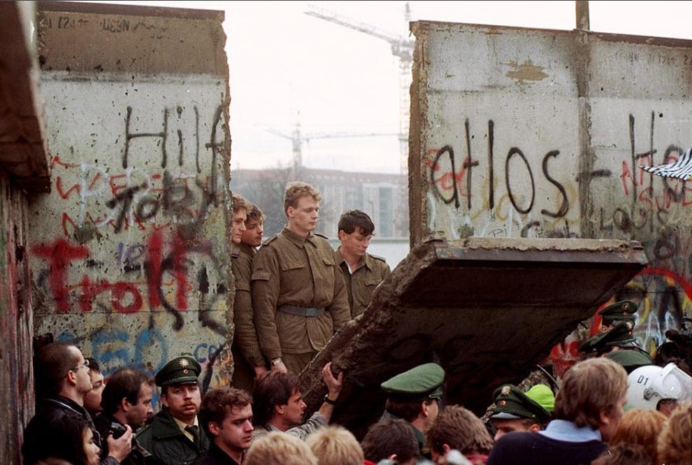 12. Солдаты пограничной службы Восточной Германии стоят у открытой части Берлинской стены, которую демонстранты пытаются снести у Бранденбургских ворот 11 ноября 1989 года. (Lionel Cironneau, AP)