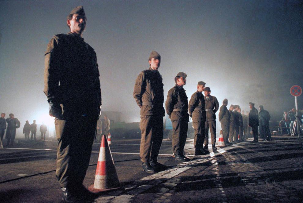 13. Солдаты Восточной Германии охраняют границу у Ostpreussendamm утром 14 ноября 1989 года, где рабочие Восточной Германии устанавливают проход через стену. Сотни жителей Восточного Берлина хлынули через ворота в западную часть разделенного города. (Thomas Kienzle, AP)