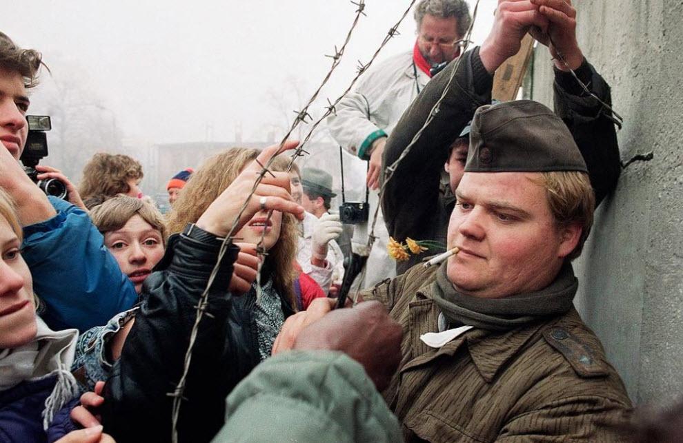 15. Солдат пограничной охраны Восточной Германии раздает колючую проволоку, которую он срезал с Берлинской стены у прохода Ostpreussendamm в Берлине 14 ноября 1989 года. (John Gaps III, AP)