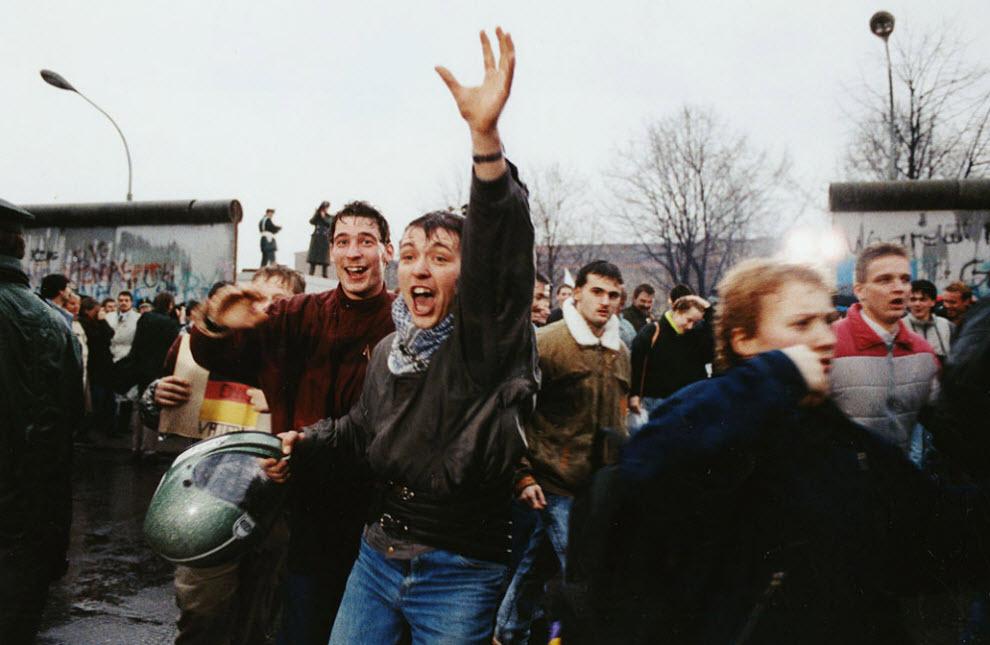 16. Молодые жители Восточного Берлина кричат от радости, пробегая через проход в Западный Берлин у Бранденбургских ворот 23 декабря 1989 года. Тогда новое правительство Восточной Германии пообещало полностью открыть ворота к Рождеству. (Hansjoerg Krauss, AP)