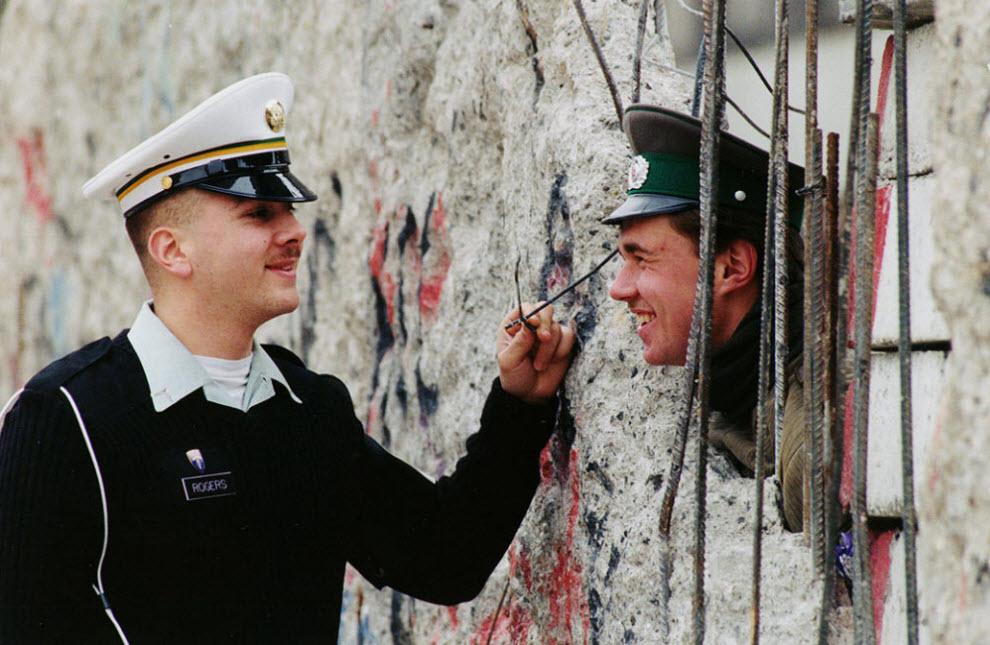 17. Служащий США Стив Роджерс из Оакланда. Калифорния, разговаривает с солдатом пограничной службы Восточной Германии Майком Стаапсом, который выглядывает из отверстия в восточной части Берлинской стены 26 марта 1990 года. (Herbert Proepper, AP)