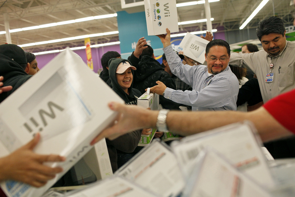 1. Марио Янез (второй справа) и управляющий пекарней Ричард Силва (справа) передают игровые приставки «Wii» и «Wii Fit» возбужденным покупателям в пятницу 27 ноября в магазине «HEB McCreless Market» в Сан Антонио, штат Техас. (San Antonio Express-News / Lisa Krantz)