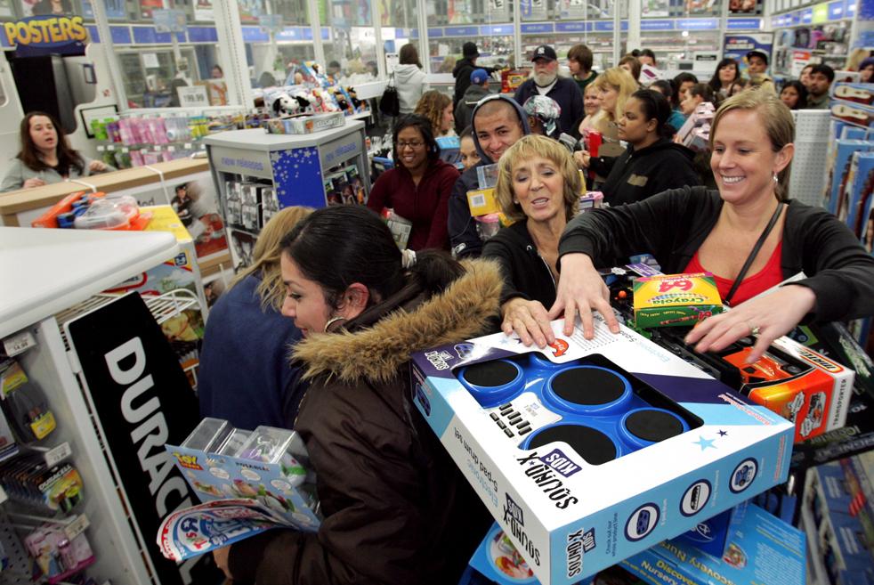 """9. Дженифер Байкуист (справа) и ее мама Дебби Моррисон (в центре) пытаются не уронить игрушки из своей тележки в магазине «Toys """"R"""" Us» в пятницу 27 ноября в Тахоме. (The News Tribune / Janet Jensen)"""