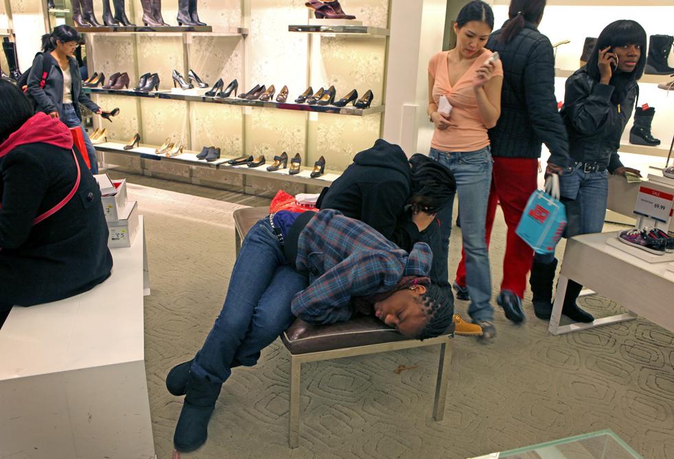 16. 12-летняя Ванесса Файемиво (слева) и ее сестра 14-летняя Вивиан Адемола (обе из Роздейла, Нью-Йорк) заснули в ожидании, пока друзья закончат выбирать обувь в магазине «Macy's» в Нью-Йорке в пятницу 27 ноября. «AP / David Goldman»