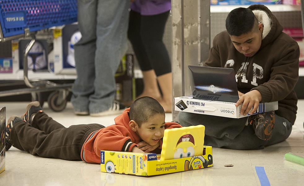 """17. Братья Дарвин (слева) и Цезарь Картагена из Федерал Уэй играют с ноутбуками в магазине «Toys """"R"""" Us» в Туквиле, штат Вашингтон, недалеко от Сиэтла в пятницу 27 ноября. (AP / Stephen Brashear)"""