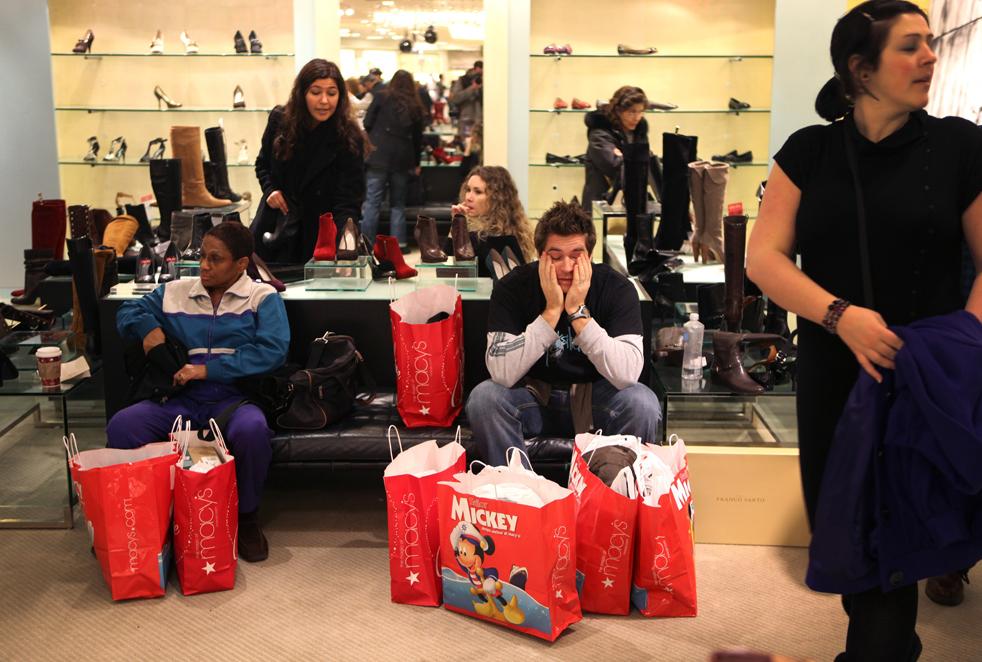 19. Сиаран Смит (в центре) из Дублина, Ирландия, отдыхает от почти пяти часов шоппинга, пока ждет свою жену, которая выбирает обувь в магазине «Macy's» в Нью-Йорке в пятницу 27 ноября. (AP / David Goldman)