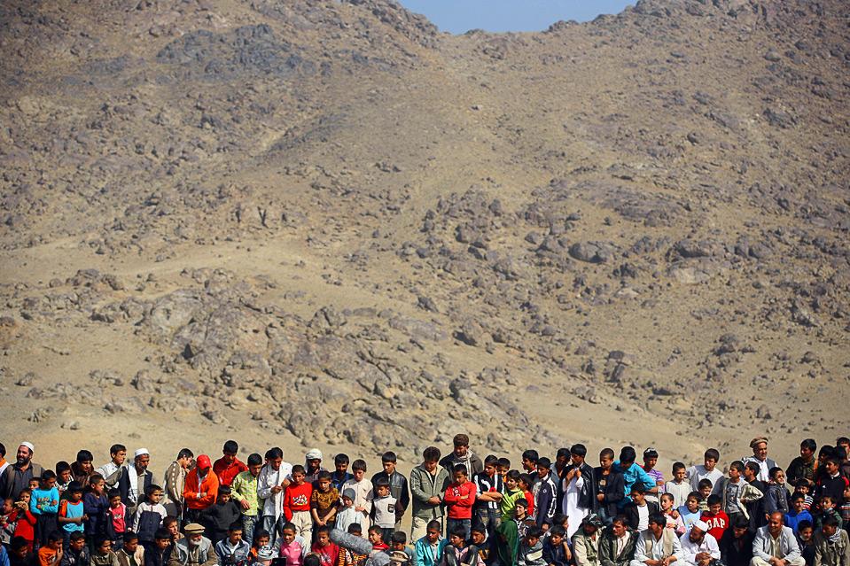 9) Зрители наблюдают, как афганские игроки в бузкаши пытаются завладеть обезглавленным козлом на матче 6 ноября в Кабуле. (Majid Saeedi/Getty Images)