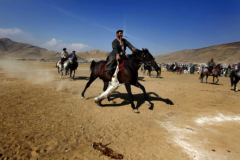 13) Афганский наездник тащит безголового козла в специальный круг, чтобы получить очко, во время игры бузкаши на окраине Кабула 6 ноября. (REUTERS/Jerry Lampen)