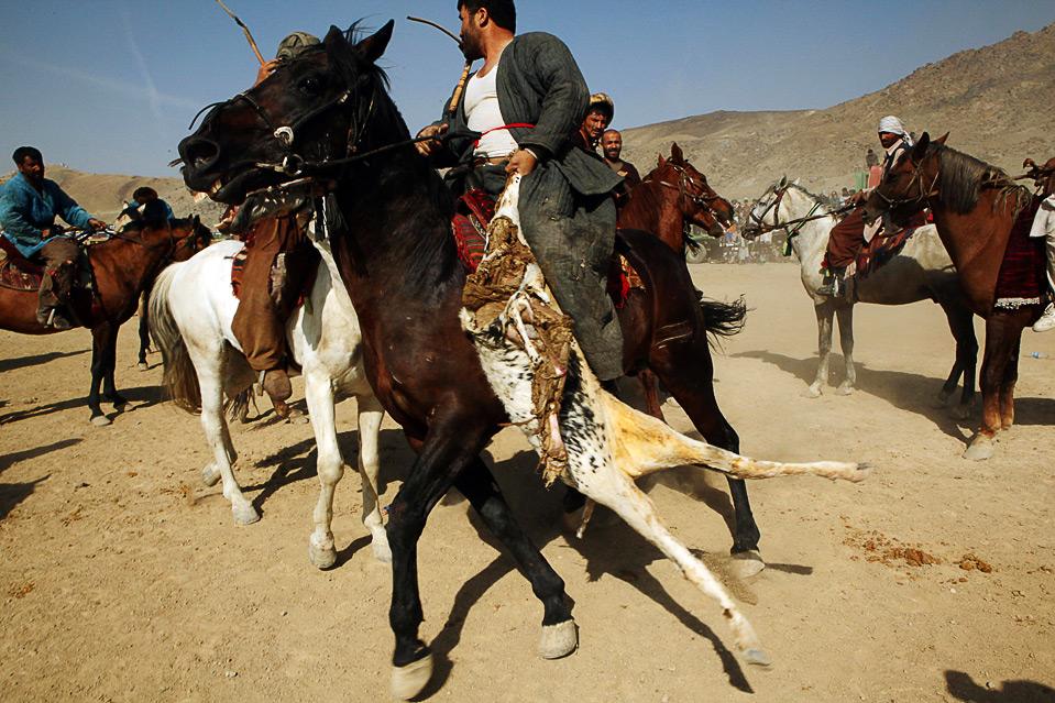 14) Афганские игроки в бузкаши верхом на лошадях борются за право обладания обезглавленным козлом на игре 6 ноября. (Majid Saeedi/Getty Images)