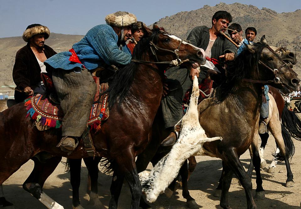 15) Афганские игроки в бузкаши тащат безголовое тело козла в игре в Кабуле 6 ноября. (AP Photo/Farzana Wahidy)