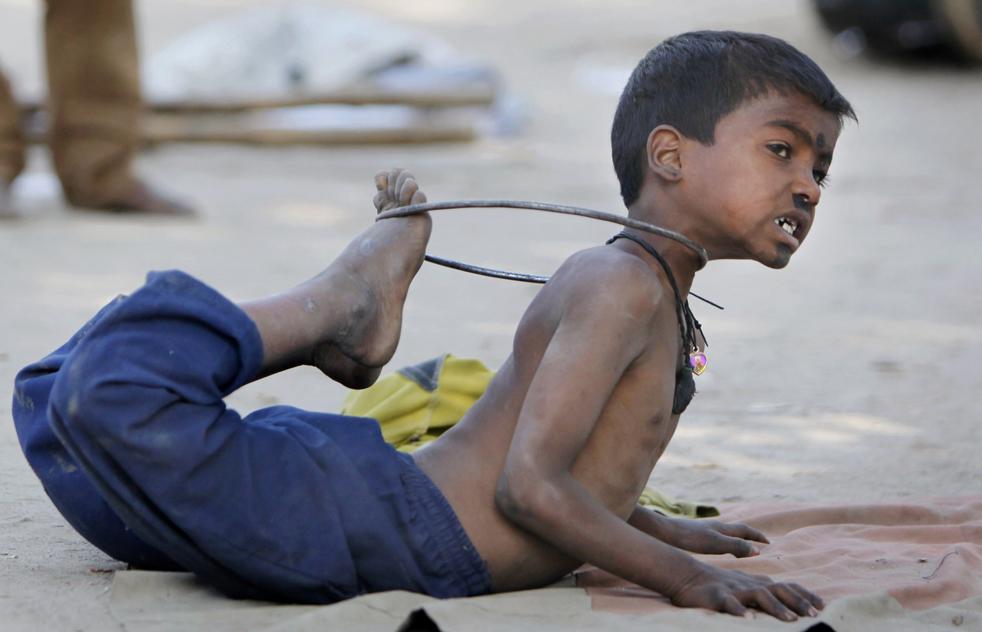 2. Бездомный мальчик демонстрирует акробатические умения с помощью железного прута на улице в Катманду, Непал, в четверг 19 ноября. (AP/Gemunu Amarasinghe)