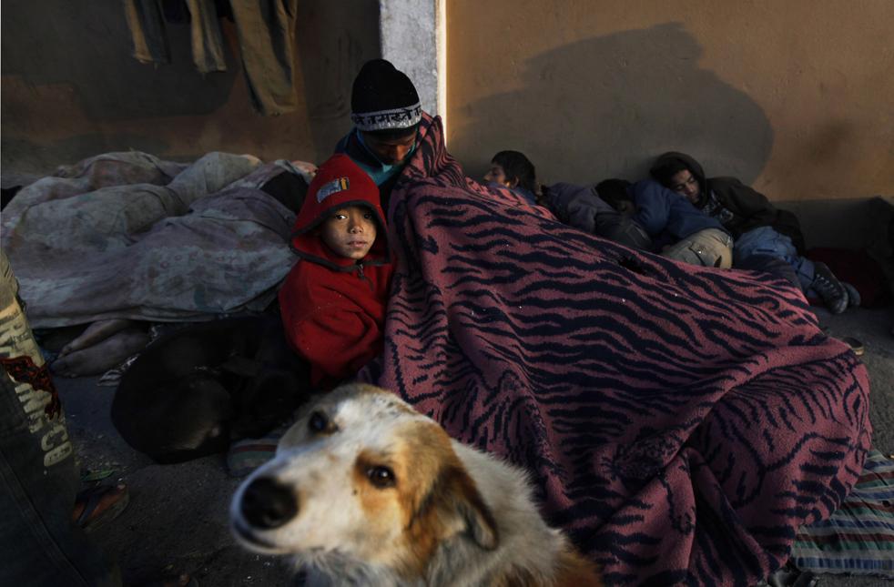 3. Бездомная собака лежит рядом с группой беспризорников на тротуаре в Катманду, Непал, в пятницу 20 ноября. (AP/Gemunu Amarasinghe)