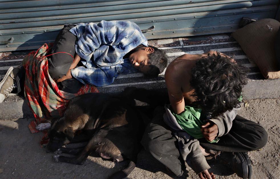 5. Бездомный ребенок спит рядом с бездомной собакой, пока другой ищет блох в своей одежде в Катманду, Непал, в четверг 19 ноября. (AP/Gemunu Amarasinghe)