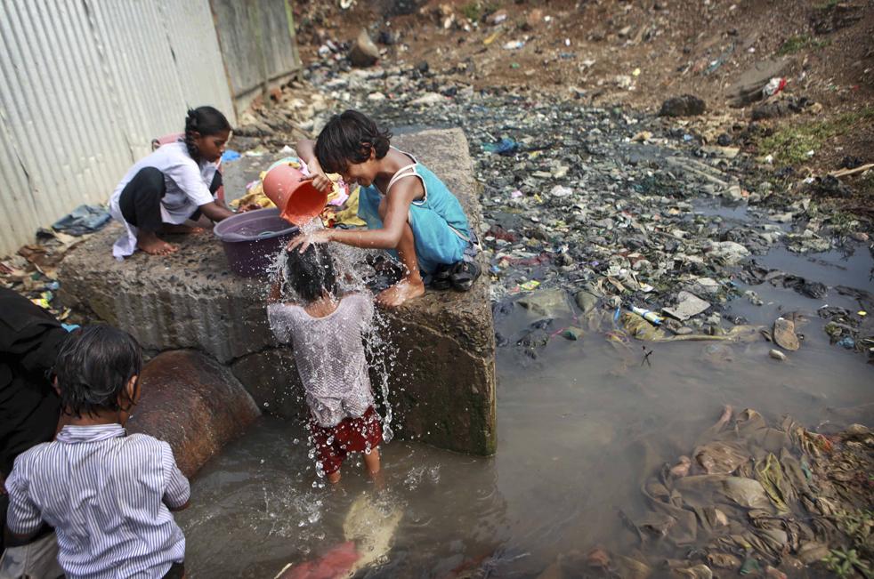 9. Дети купаются в сточных водах вокруг канализации в Мумбаи, Индия, в среду 18 ноября. (AP/Rafiq Maqbool)