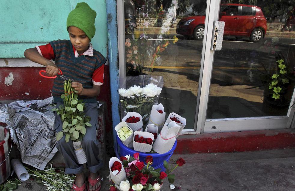 10. 8-летняя Динеш обрезает розы у цветочного магазина в Гаухати, Индия, в среду 18 ноября. (AP/Anupam Nath)