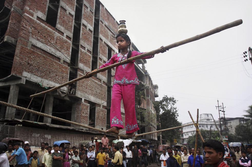 11. 6-летняя Шила идет по канату во время уличного представления в Гаухати, Индия, в среду 18 ноября. (AP/Anupam Nath)