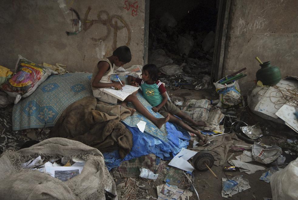 13. Дети учатся во дворе среди собранного для переработки мусора в Хайдарабаде в пятницу 20 ноября. (AP/Mahesh Kumar A)