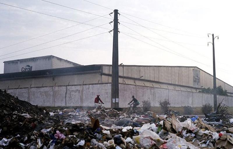 6.Здание компании «Каргилл» - одного из нескольких крупных экспортеров в Кот-д'Ивуар – за высокими стенами. В «Каргилле» запрещена эксплуатация детского труда – официальный рабочий возраст 18 лет.  Однако этот закон игнорируют. Шоколадная индустрия, правительства и организации по защите гражданских прав создали международную кампанию, направленную на решение проблемы, однако детский труд по-прежнему эксплуатируют. Крупные компании вроде «Каргилла» не владеют плантациями, так что официально они не нанимают работников. Они просто скупают бобы какао у рабочих. И все же борцы за права человека говорят, что ответственность за улучшение условий труда лежит как раз на подобных компаниях. (Jessica Dimmock / VII Network)