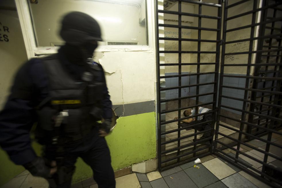 7. Офицер полиции проходит мимо задержанного в центре предварительного заключения в Тихуане. (AP/Guillermo Arias)