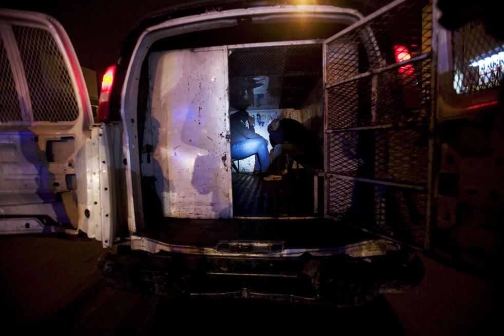 9. Арестованные в полицейском фургоне закрывают лица после задержания в Тихуане. (AP/Guillermo Arias)