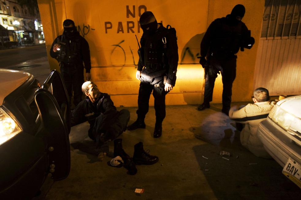 10. Офицеры полиции обыскивают подозреваемых на предмет наркотиков и оружия в мексиканском городе Зоне Норте. (AP/Guillermo Arias)