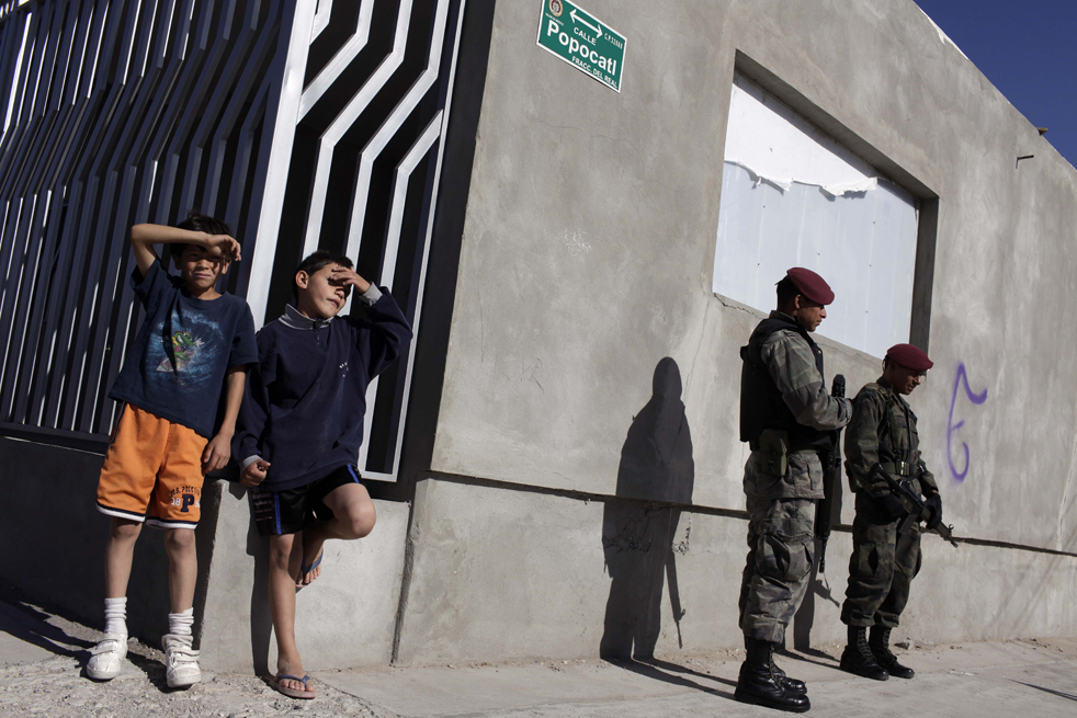 13. Мальчики смотрят на солдат, которые стоят на страже на месте убийства человека в Сьюдад-Хуаресе. (AP/Rodrigo Abd)