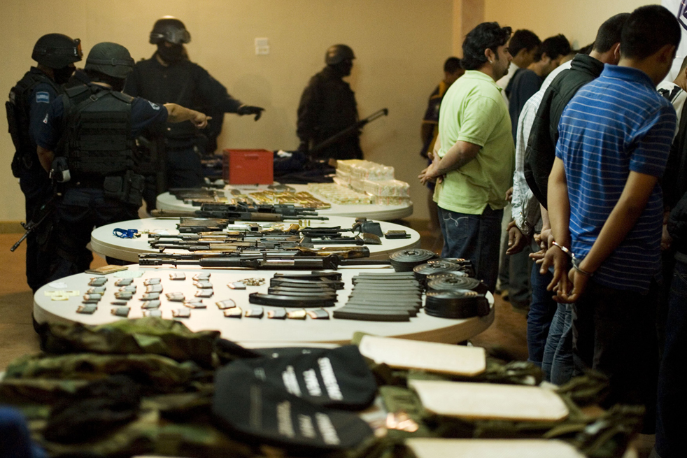 15. Офицеры полиции указывают на конфискованное у подозреваемых наркоторговцев оружие после пресс-конференции в Текате. Федеральная полиция Мексики арестовала 21 подозреваемого в перестрелке с федеральной полицией в Текате. (AP/Guillermo Arias)