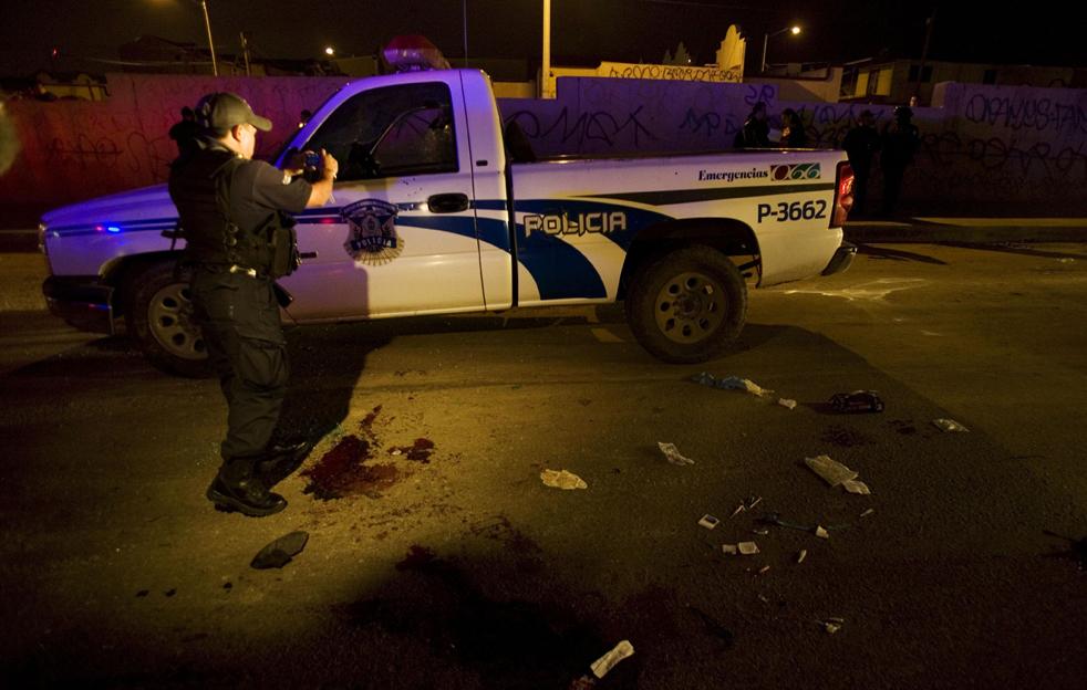 17. Офицер федеральной полиции фотографирует место преступления в Тихуане, где ранили двух офицеров полиции. (AP/Guillermo Arias)