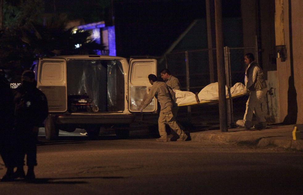 18. Работники морга несут тело неопознанного человека, которого убили в Сьюдад-Хуаресе. (AP/Rodrigo Abd)