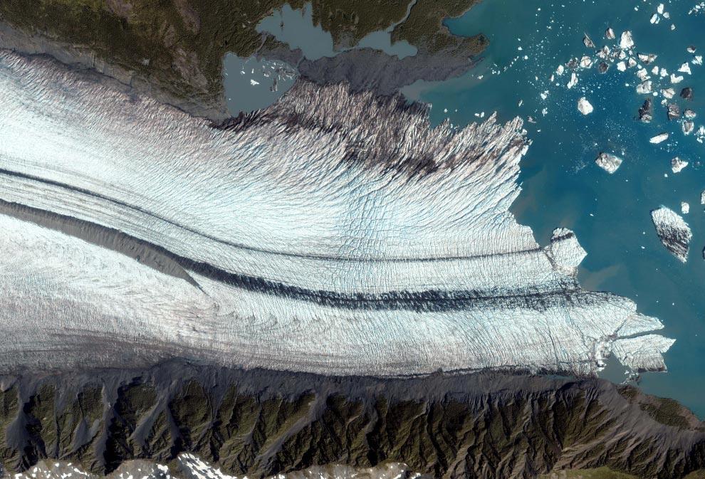 2) Снимок Медвежьего Ледника Кенайского полуострова залива Аляска сделан 8 августа 2005 года со спутника IKONOS. На этом снимке показана область вымывания, где ледник начинает таять. Поднимающееся вверх по склону подножье ледника изрешечено расселинами – трещинами во льду, появившимися из-за перемещений ледника по неровной поверхности. Ближе к середине ледника начинаются темно-серые полосы. По мере перемещения ледника они наполняются грязью и обломками скал. Когда сходятся два ледника, как и в нашем случае, грязь и обломки вытесняются на поверхность из параллельных полос или срединных отложений. (Снимок со спутника IKONOS GeoEye)