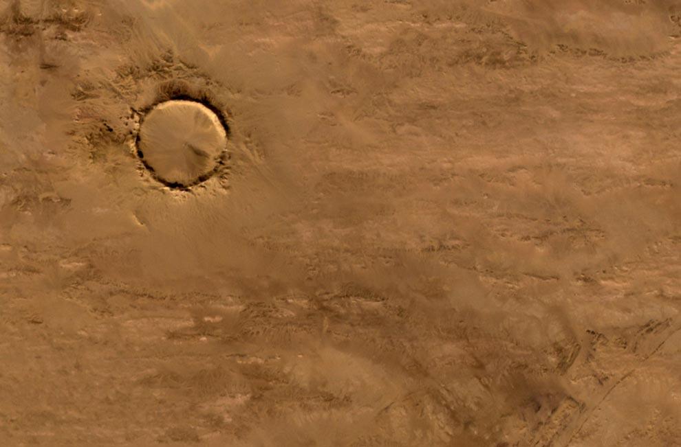 """4) Этот кратер находится в глубине пустыни Сахара. Имея форму почти идеального круга, его ширина составляет 1.9 километра (1.2 мили), а высота внешнего края - 100 метров (330футов). Этот кратер располагается на обширной плоскости скальной породы, образовавшейся за сотни миллионов лет до появления первых динозавров на Земле. Современные геологи давно спорят о причинах возникновения этого кратера, некоторые из них склоняются к идее вулканического образования кратера. Однако, при более детальном изучении структуры, можно обнаружить, что эта окаменелая """"лава"""" – в действительности гора, расплавленная от удара метеорита о Землю. Система ASTER, установленная на спутнике Terra агентства NASA сделала снимок кратера Tenoumer в Мавритании 24 января 2008 года. (NASA,Jesse Allen, NASA/GSFC/METI/ERSDAC/JAROS, U.S./Japan ASTER Science Team)"""