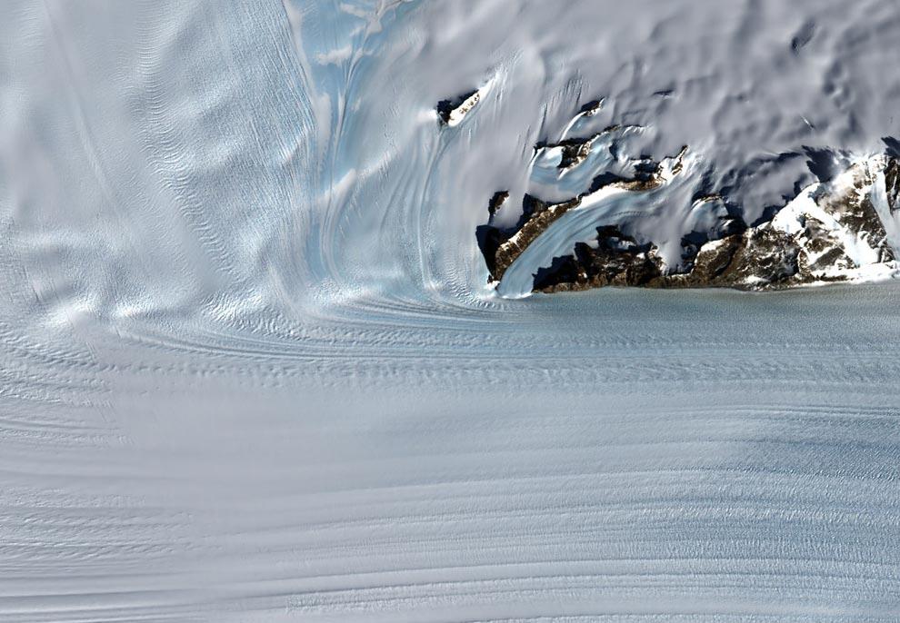 11) Непомерно высокие Антарктические горы направляют поток ледникового щита в  быстродвижущуюся ледяную реку под названием Byrd Glacier, расположенной вблизи станции McMurdo - Главной Антарктической Научно-Исследовательской Станции Соединенных Штатов. Ледник стремительно несется в Трансатлантических Горах по глубокому,  15-метровому в ширину каналу, создавая обрушивающий камни ледяной поток, протяженностью в 100 миль. Этот снимок, сделанный 24 декабря1999 года спутником Landsat 7, показывает часть текущей через Трансатлантические Горы ледяной реки Byrd Glacier (Jesse Allen, Landsat Image Mosaic of Antarctica,LIMA)
