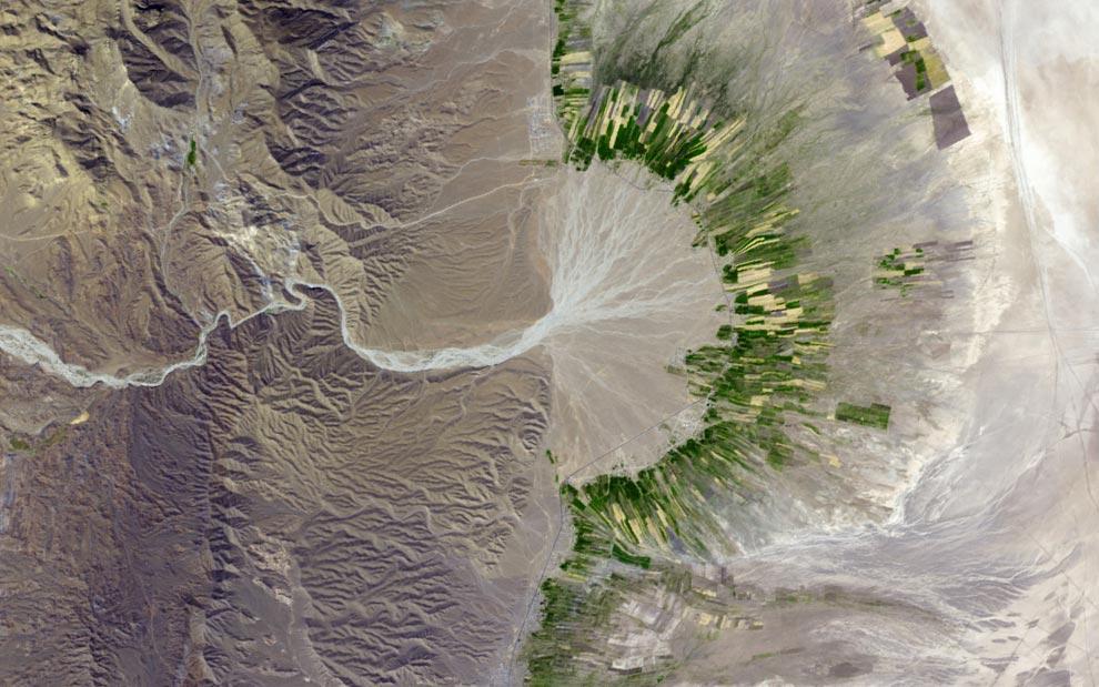 15) Это снимок юго-восточной провинции Фарс на юге Ирана, сделанный в поддельно-естественных тонах, отображает русло реки, прорезающееся на северо-восток сквозь засушливые земли гор. Широкая полоса земли, покрытая буйной растительностью сельскохозяйственных угодий, повторяет изгибы сухой дельты и раскидывается вдоль дороги, идущей параллельно линии хребта. Приграничные области долины ярко-зеленой сельскохозяйственной зоны плавно переходят в бледную зелень (или оросительные каналы). Снимок был сделан системой ASTER со спутника Terra агентства NASA 12 октября 2004 года (NASA/Jesse Allen, NASA/GSFC/METI/ERSDAC/JAROS, U.S./Japan ASTER Science Team)