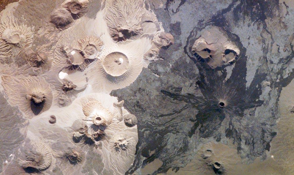 """19) Гора Harrat Khaybar в Саудовской Аравии содержит множество типов вулканической породы и впечатляющих рельефов земной коры. Некоторые из них представлены на этой фотографии, сделанной астронавтом с Международной орбитальной станции 31 марта 2008 года. Jabal (""""гора"""" по-арабски) al Qidr формировалась из потоков лавы темного жидкого базальта нескольких извержений. Jabal Abyad, в центре снимка, образовалась из более густой лавы, богатой кварцем, называемой также риолитом. (NASA-JSC)"""
