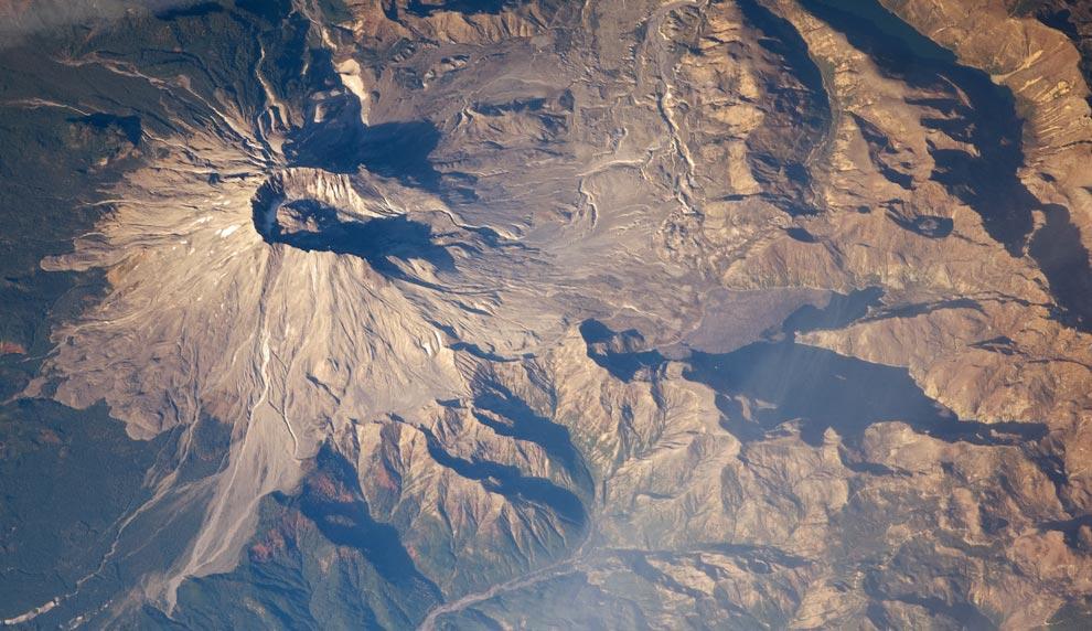 21) 18 мая 1980 года, во время извержения вулкана Сан-Геленс (Mount St. Helens), северная сторона обвалилась, и массивный поток из камня, ила и вулканических обломков понесся вниз по горе. Эта фотография, сделанная 28 октября 2008 года астронавтом с Международной орбитальной станции, показывает нам место происшествия почти через три десятилетия после извержения – все еще заметен ущерб, нанесенный лесонасаждениям в области схода лавины. С южной стороны горы ландшафт покрыт густым зеленым лесом, в то время как с северной стороны растительность редкая, особенно на больших высотах. (NASA/JSC)