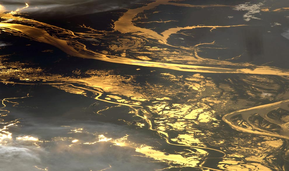 23) На этой фотографии, сделанной астронавтом 19 августа 2008года, в Амазонке и поймах многочисленных озер отражается яркий блеск лучей заходящего солнца. Здесь захвачено порядка 150 километров Амазонки, на расстоянии приблизительно 1000 километров в глубь материка от Атлантического океана. Этот кадр был пойман экипажем 17 экспедиции Международной орбитальной станции 19 августа 2008года. (NASA/JSC)