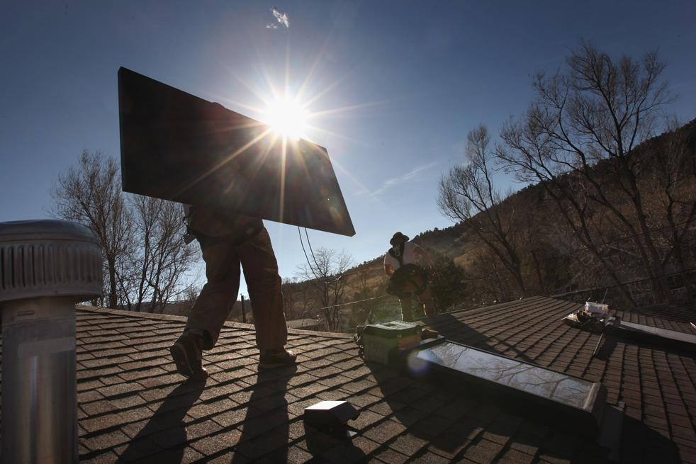 9. Уэйд Эндрюс – работник компании «Namaste Solar» - несет солнечную панель на крыше жилого дома 4 марта в Болдере, штат Колорадо. Компании по выработке возобновляемой энергии (такие как  «Namaste») получат дополнительные фонды на создание «зеленых» инициатив из федерального пакета экономических стимулов. (Getty Images / John Moore)