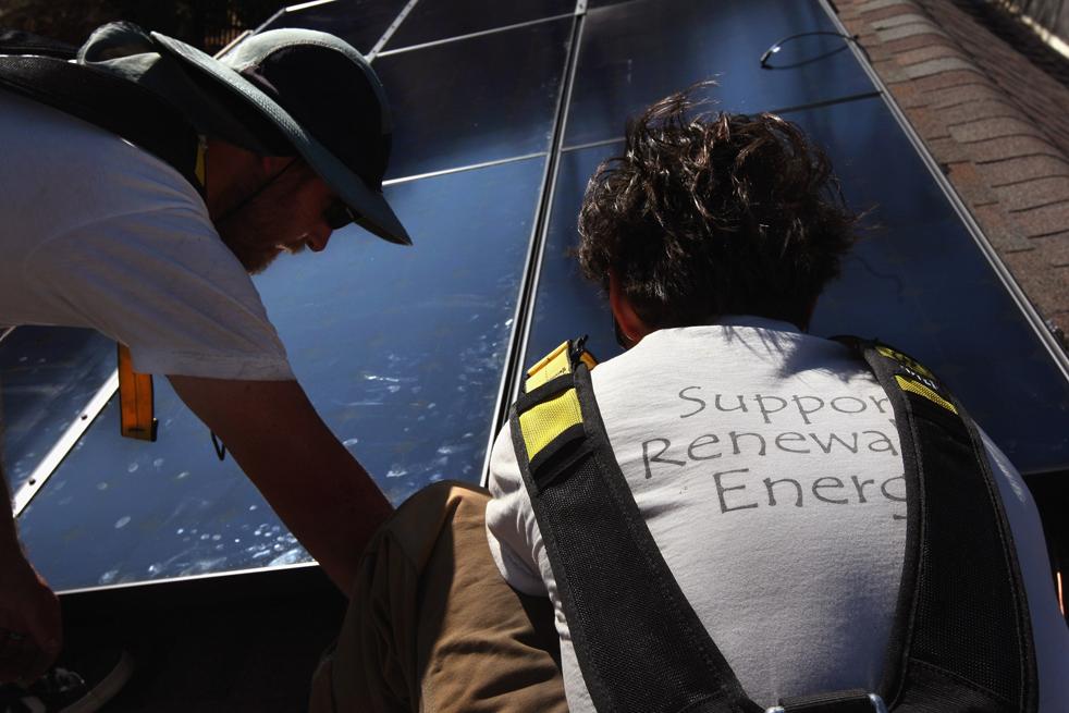 12. Монтажники из компании «Namaste Solar» ставят солнечную панель на крышу дома 4 марта в Болдере, штат Колорадо. Компании по выработке возобновляемой энергии (такие как  «Namaste») получат дополнительные фонды на создание «зеленых» инициатив из федерального пакета экономических стимулов. (Getty Images / John Moore)