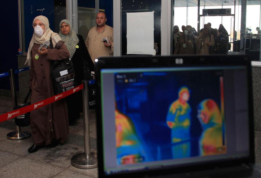 4. Паломники проходят мимо прибора с тепловыми датчиками для определения температуры тела по прибытии в аэропорт Джеддах в Саудовской Аравии 10 ноября 2009 года. Ожидая, что к святым землям Мекки на ежегодное паломничество Хадж прибудет около трех миллионов паломников из 160 стран, власти Саудовской Аравии усилили меры по охране здоровья в аэропортах и морских портах, а также создали в госпитале короля Сауда специальное отделение на 300 коек для больных свиным гриппом. (REUTERS/Susan Baaghil)