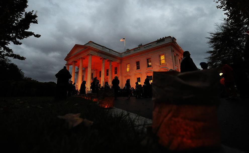 6. Белый дом подсвечен оранжевым в честь Хэллоуина в Северном крыле, где собралось много людей 31 октября 2009 года. (JEWEL SAMAD/AFP/Getty Images)
