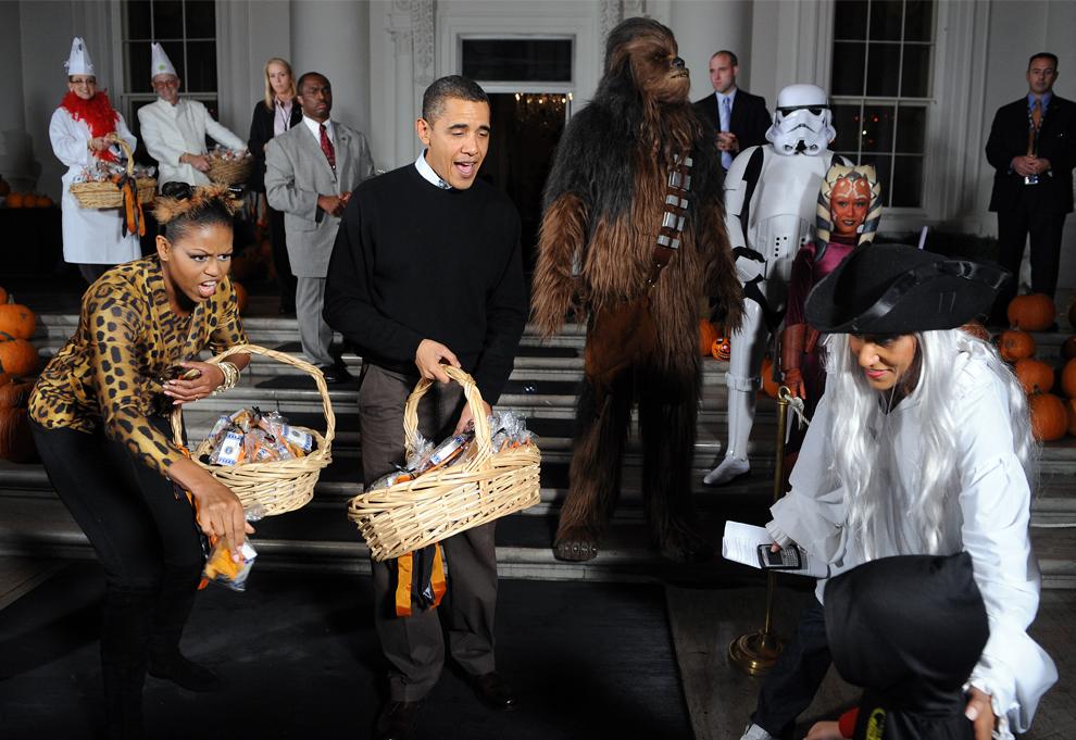 8. Президент США Барак Обама и первая леди Мишель Обама приветствуют детей у северного входа в Белый дом в Хэллоуин в Вашингтоне, округ Колумбия, 31 октября 2009 года. Президентская семья поприветствовала более 2000 детей из школ Вашингтона, Мэриленда и Виржинии и их семей во время Хэллоуина. (JEWEL SAMAD/AFP/Getty Images)