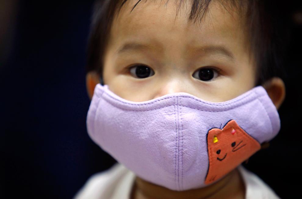 17. Мальчик в маске ожидает своей очереди на вакцинацию в больнице в Тайбэе, Тайвань, 9 ноября 2009 года. В тот день правительство Тайваня начало вакцинацию против вируса H1N1 для детей в возрасте от 6 месяцев до года. (REUTERS/Nicky Loh)